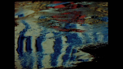 Still from Abstract in Concrete (1952). Director John Arvonio filmed lights reflecting on street puddles, creating the illusion of an oil painting.